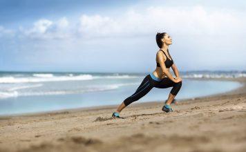 Deportista haciendo estiramiento en la playa