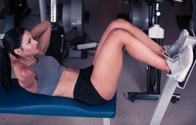 Crunch abdominal en banco de gimnasio. Entrenamiento